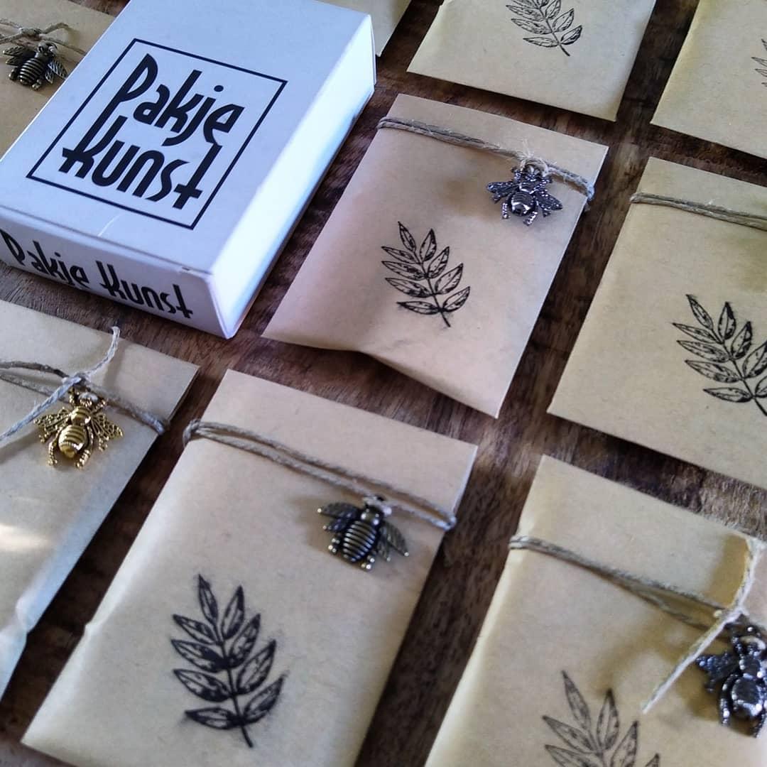 Cadeautjes in bruin craftpapier met een stempel van een blad en een bedel van een bij. In het midden van de foto een pakje kunst.